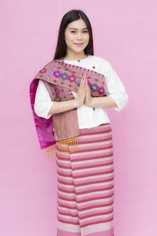 Ritratto della ragazza asiatica nella preghiera tailandese tradizionale del vestito isolata su fondo rosa
