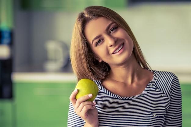 Ritratto della ragazza attraente che tiene una mela.
