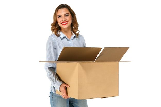 Ritratto della ragazza attraente sveglia che tiene grande scatola di cartone in sue mani