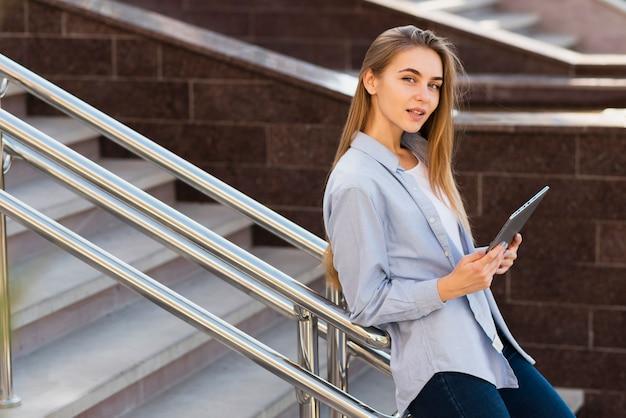 Ritratto della ragazza bionda che tiene una compressa e che esamina fotografo