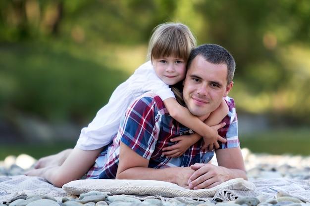 Ritratto della ragazza bionda sveglia che abbraccia giovane padre sulla sponda del fiume pebbled il giorno di estate luminoso sul fondo verde vago del bokeh degli alberi. felici rapporti familiari, amore, cura e perfetto concetto di vacanza.
