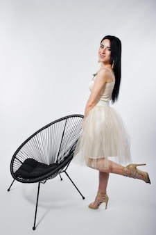 Ritratto della ragazza castana sul vestito beige con la sedia isolata su bianco.