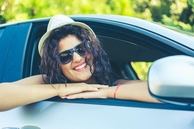 Ritratto della ragazza che sorride nell'automobile