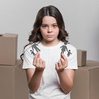 Ritratto della ragazza che tiene famiglia di carta