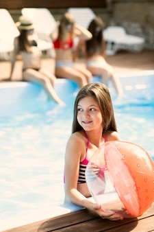 Ritratto della ragazza che tiene un pallone da spiaggia