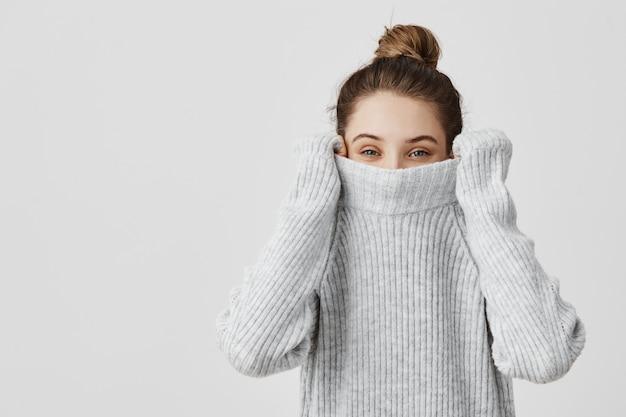 Ritratto della ragazza che tira il suo maglione d'avanguardia sopraelevato divertendosi. donna con i capelli legati in topknot essendo infantile scomparendo nei suoi vestiti guardando da sotto. concetto di felicità