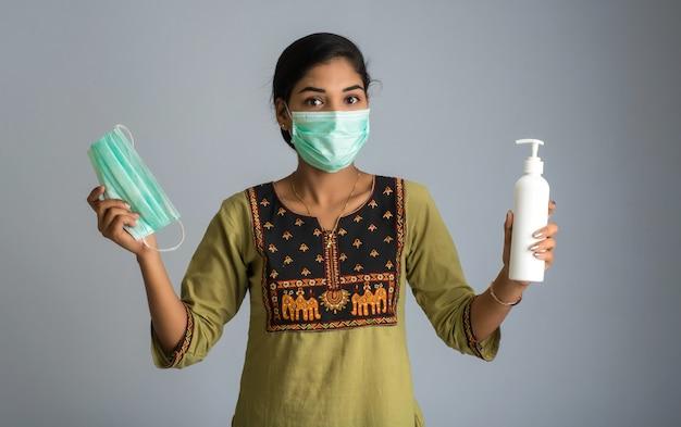 Ritratto della ragazza che usando o che mostra maschera e gel igienizzante da una bottiglia per la pulizia delle mani.