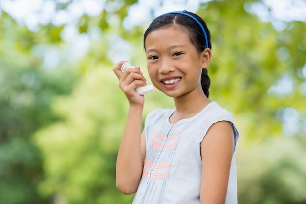 Ritratto della ragazza che utilizza un inalatore di asma nel parco