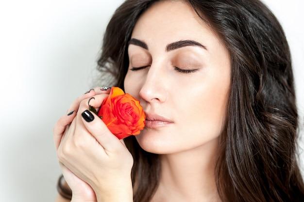 Ritratto della ragazza dai capelli rossi che ride con rose arancioni