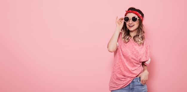 Ritratto della ragazza dei pantaloni a vita bassa in vetri sulla parete rosa