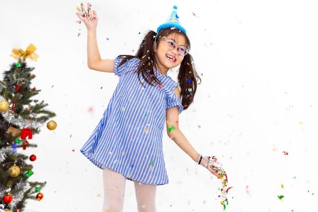 Ritratto della ragazza del bambino che sorride e divertente su fondo bianco