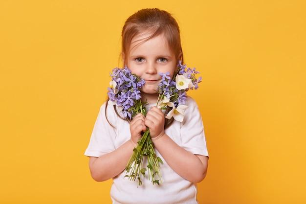 Ritratto della ragazza del bambino con il mazzo dei fiori del giardino isolati sopra giallo