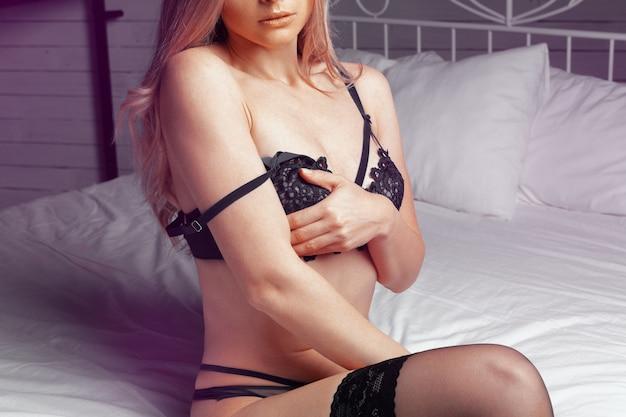 Ritratto della ragazza del modello di moda all'interno in biancheria attraente del pizzo che si siede sul letto