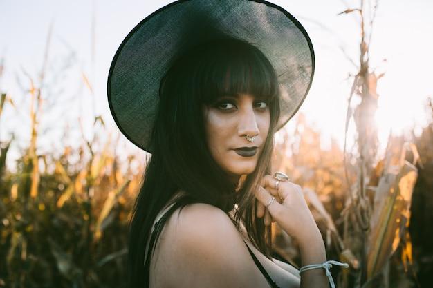 Ritratto della ragazza della strega del costume di halloween in un campo di mais al tramonto. bella giovane donna seria in cappello delle streghe con lunghi capelli neri e labbra scure