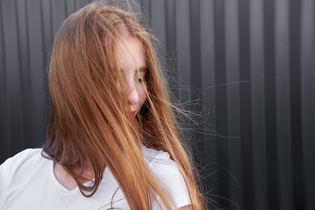 Ritratto della ragazza della testarossa in camicia bianca con le labbra dipinte rosse sul fondo grigio del pannello del metallo.