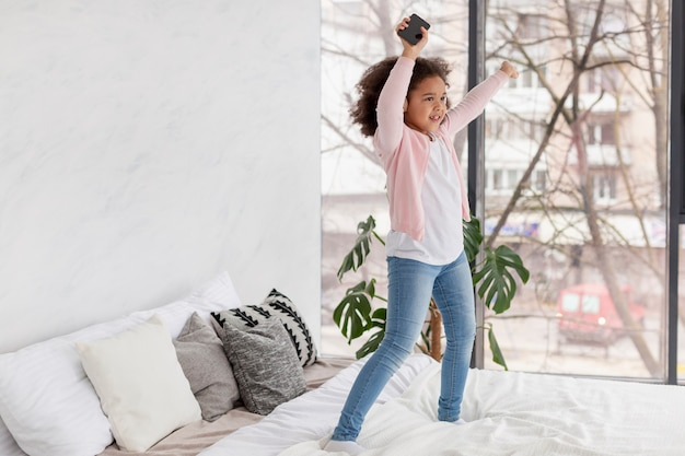 Ritratto della ragazza felice che salta a letto