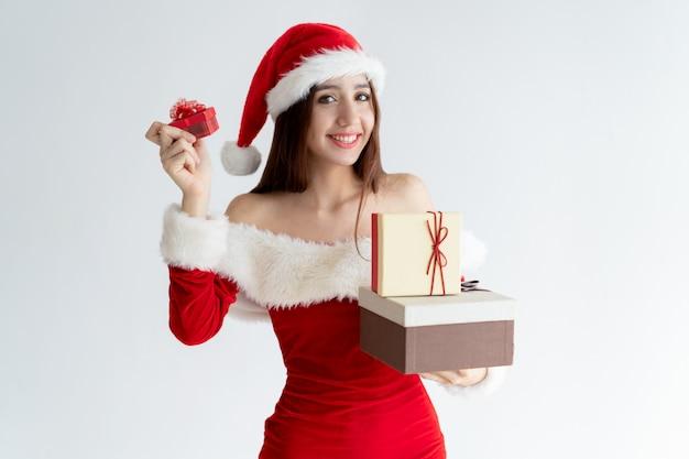 Ritratto della ragazza felice in vestito dall'assistente di santa che mostra i contenitori di regalo