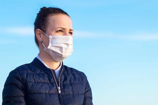 Ritratto della ragazza premurosa pensierosa seria, giovane bella donna nella maschera protettiva sterile medica sul suo fronte sul fondo del cielo blu, spazio della copia. coronavirus, covid-19, epidemia, concetto di virus.