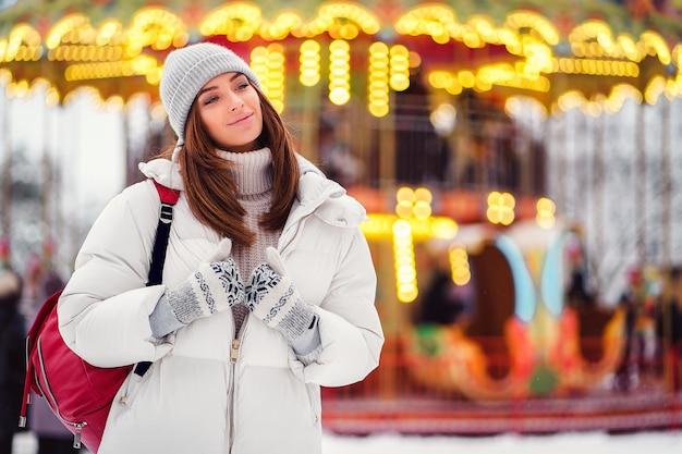 Ritratto della ragazza sbalorditiva che cammina sulla città di festa