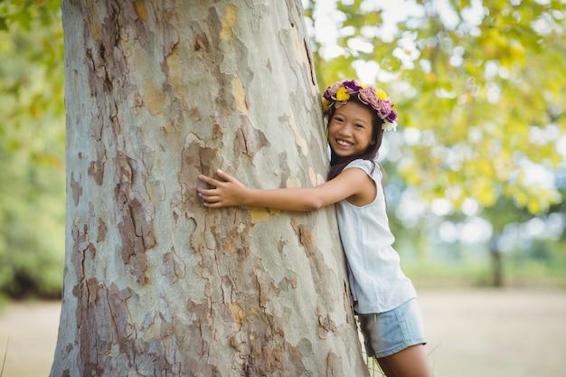 Ritratto della ragazza sorridente che abbraccia il tronco di albero in parco