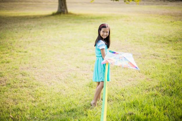 Ritratto della ragazza sorridente che gioca con l'aquilone in parco