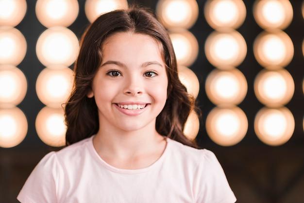 Ritratto della ragazza sorridente contro luce incandescente della fase
