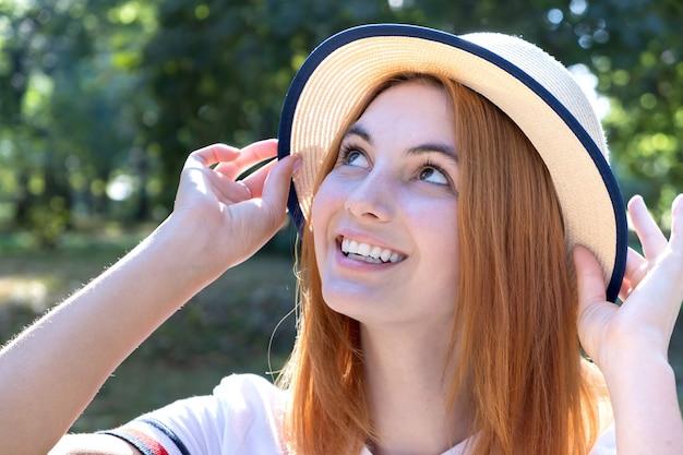 Ritratto della ragazza sorridente felice con capelli rossi e in cappello giallo all'aperto nel parco di estate.