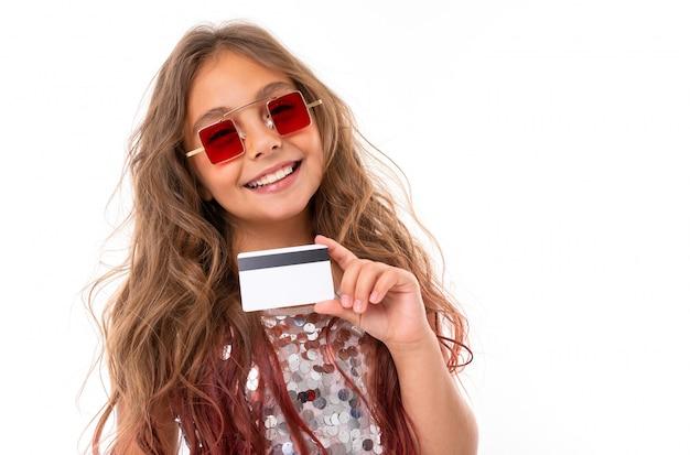 Ritratto della ragazza sorridente in occhiali da sole rossi quadrati che giudicano la carta assegni di plastica isolata