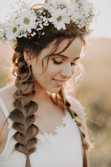 Ritratto della ragazza sorridente in vestito bianco con la corona e le trecce floreali di estate al tramonto nel campo
