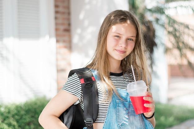 Ritratto della ragazza splendida sorridente che esamina macchina fotografica con la bevanda e la borsa fredde della tenuta