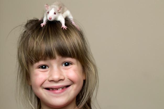 Ritratto della ragazza sveglia divertente sorridente felice del bambino con il criceto bianco del topo dell'animale domestico sulla testa sul fondo leggero dello spazio della copia della parete.
