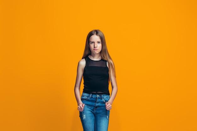 Ritratto della ragazza teenager arrabbiata su un'arancia