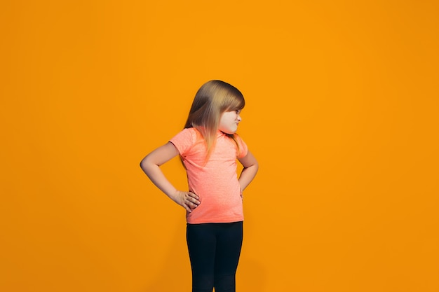Ritratto della ragazza teenager arrabbiata su uno spazio arancio