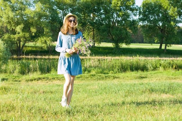 Ritratto della ragazza teenager con il mazzo dei wildflowers