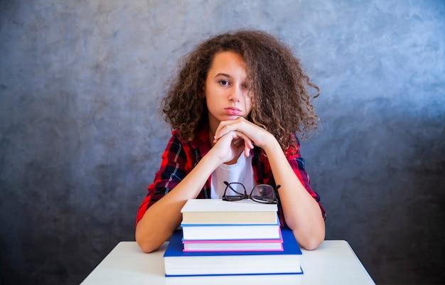 Ritratto della ragazza teenager dei capelli ricci sopra il libro