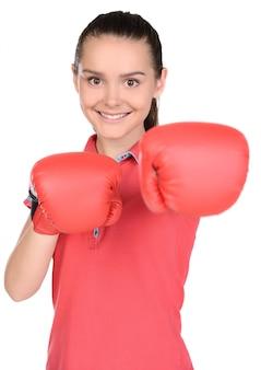 Ritratto della ragazza teenager in guantoni da pugile di addestramento di pugilato.