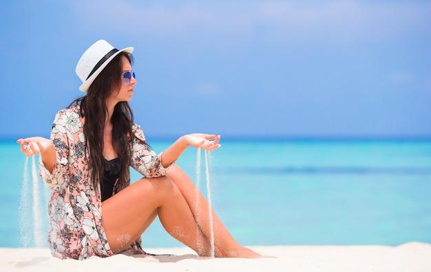 Ritratto della sabbia di lancio della giovane donna sulla spiaggia durante le vacanze estive