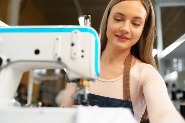 Ritratto della sarta che lavora con la macchina per cucire