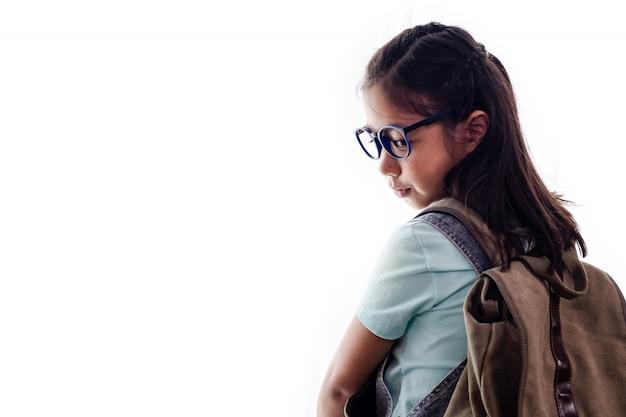 Ritratto della scolara o del bambino asiatica abbastanza astuta con i libri e lo zaino isolato