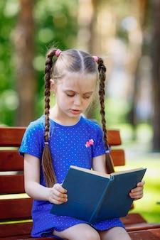 Ritratto della scolara su un libro di lettura del banco. parco cittadino di sfondo.