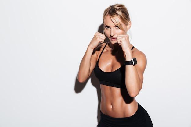 Ritratto della sportiva abbastanza concentrata che fa kickboxing