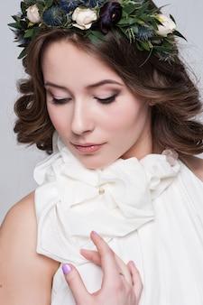 Ritratto della sposa con grandi occhi belli su bianco
