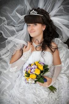 Ritratto della sposa con i capelli ricci e un bouquet da sposa di rose gialle