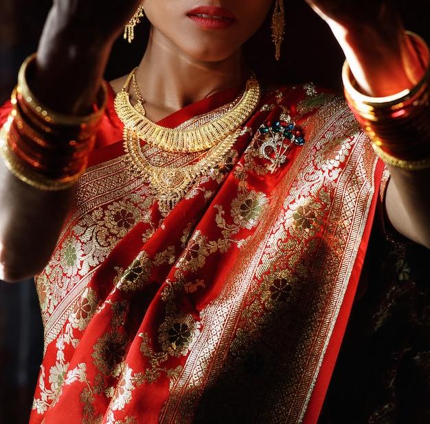 Ritratto della sposa indù in sari rosso tradizionale con acce d'oro
