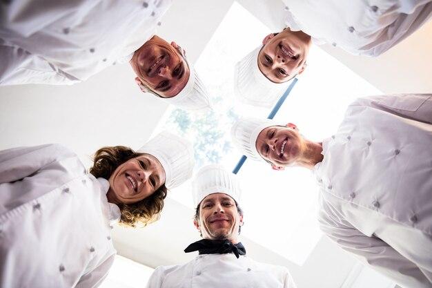 Ritratto della squadra di chef in piedi in un cerchio indossando uniformi