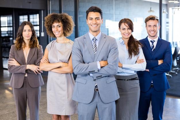 Ritratto della squadra sicura di affari che si leva in piedi nell'ufficio con le loro mani attraversate