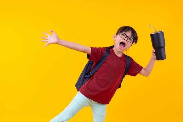 Ritratto della studentessa asiatica attraente con la borsa di scuola che tiene bicchiere d'acqua su giallo