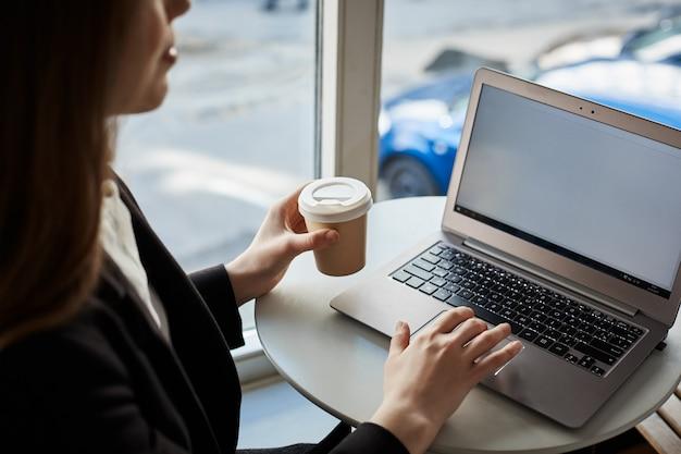 Ritratto della studentessa moderna che si siede nel caffè mentre beve il caffè e controllando la posta con il computer portatile