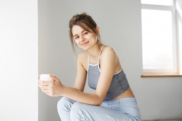 Ritratto della tazza tenente sorridente della giovane donna tenera che si siede sulla sedia sopra la parete bianca nelle prime ore del mattino.