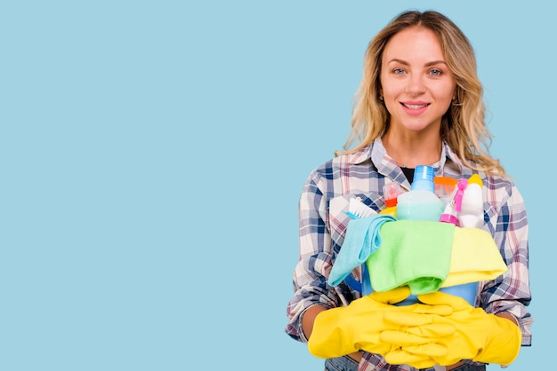 Ritratto delle attrezzature per la pulizia diritte dalla donna felice della governante nella superficie del blu